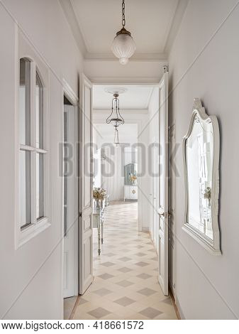 Hallway With Vintage Chandeliers Overlooking A Long Corridor With Many Doors To The Rooms.
