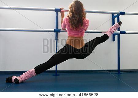 Woman siting on straddle split on bar in dance studio