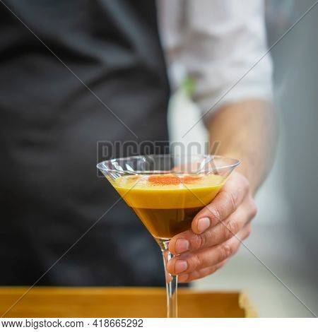 Hand Of Barista Holding Glass Of Espresso Coffee Cocktail Close-up. Alcoholic And Non-alcoholic Refr