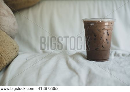 A Cup Of Iced Coffee Mocha Place On White Sofa For Relax And Refresh In The Afternoon.