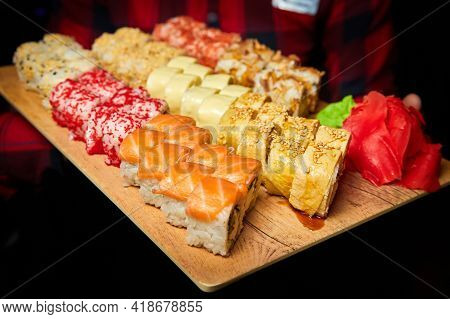 Big Set Of Sushi Rolls On A Board In The Hands Of A Waiter