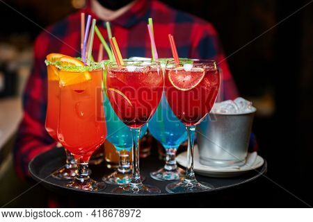 The Waiter Holds A Tray With Multicolored Alcoholic And Non-alcoholic Cocktails With Ice And Straws