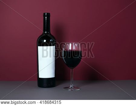 A Glass Of Red Wine On A Burgundy Background With A Bottle Of Wine In The Background. Stylish Wine A