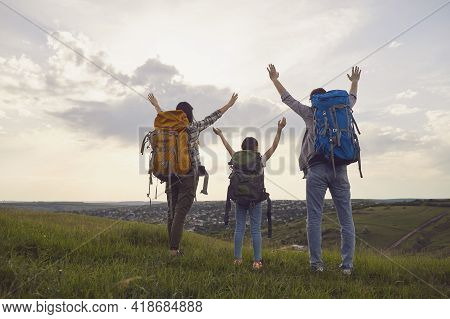 Happy Family With Backpacks On The Nature At Sunset. Hiking Family Tourism Concept.