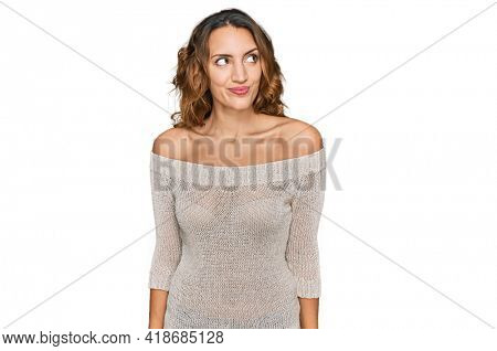 Beautiful young caucasian woman wearing casual clothes smiling looking to the side and staring away thinking.