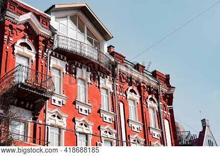 Restored Facade With Of The Red Brick Building With White Inserts And Windows And Huge Wrought Balco