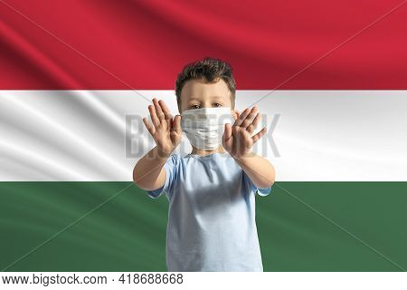 Little White Boy In A Protective Mask On The Background Of The Flag Of Hungary. Makes A Stop Sign Wi