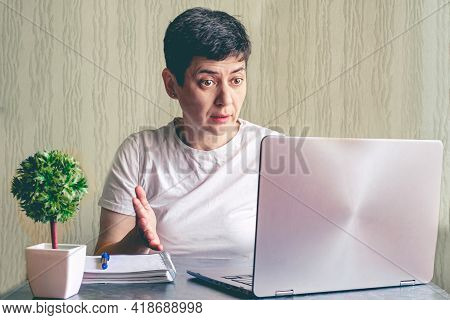 Brunette Woman With Short Hair Sits At A Table In Front Of A Laptop With And Looks Indignantly At Sc