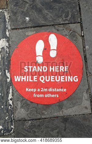 Weston-super-mare, Uk - April 9, 2021: A Sign On A Pavement Warning Those Queueing To Keep Two Metre