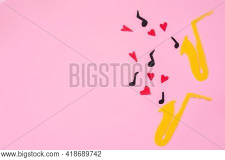 A Cutted Out Of Felt Saxophones From Which Hearts And Melodies Flew Out, On A Pink Background. Flat