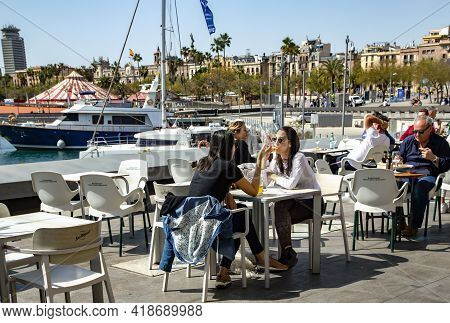 Spain, Barcelona, March, 2021: People Dine On The Open Verandas Of Cafes And Restaurants On The Port