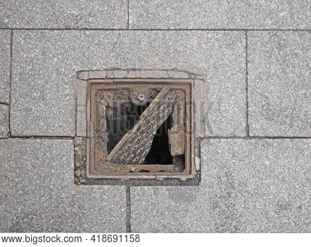 Top View Of A Broken Sewer Manhole And An Open Square Sewer Well.