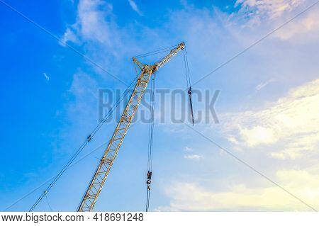 Hoisting Machine Industrial Crane Equipment Against Blue Sky At Construction Site.