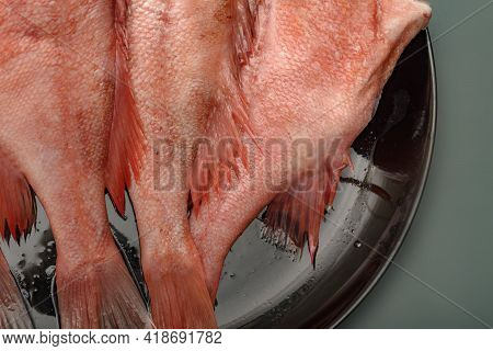 The Split Sea Bass On A Round Plate Black. Raw Red Sea Bass.