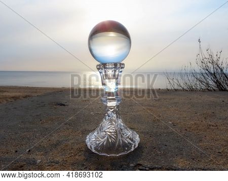 Crystal Ball On Vintage Crystal Stand On Sandy Beach At Sunset, Sun Flare Reflecting
