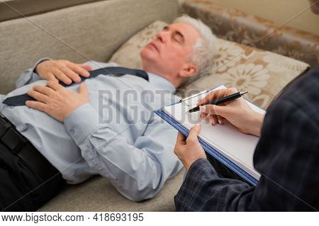 An Elderly Man Lies On A Couch During An Appointment With A Psychotherapist. An Elderly Male Patient