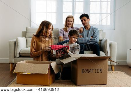 Cute Little Caucasian Boy Putting Things Like Clothes In Cardboard Box For Donation With Help Of Tee