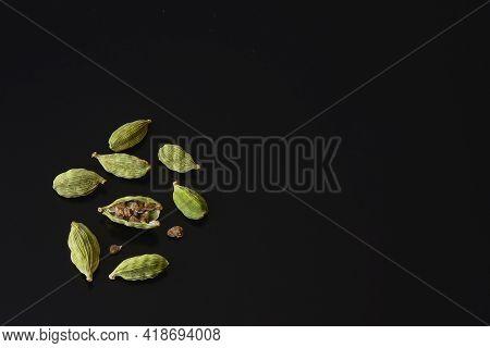 Dry Green Cardamom Seeds, Elettaria Cardamomum, Closeup. Cardamom Pods On Black Background. Organic