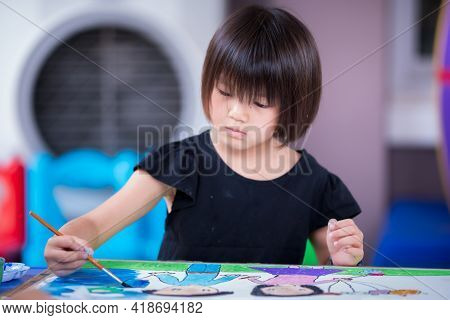 Asian Girl Aged 5-6 Is Working On Art. Kid Paint Brushes On Large Sheets Of Paper Fixed On Plywood B