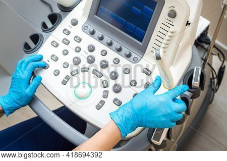 Ultrasound Machine And Hands Of A Gynecologist Close-up. Condom Ultrasound Probe For Vaginal Examina