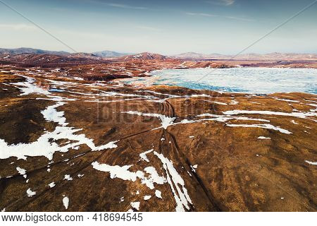 Melting Snow On The Lake And Mountains In Early Spring. Aerial Drone View. Beautiful Spring Landscap