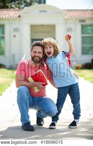 Father Supports And Motivates Son. Kid Going To Primary School. Happy Family At School Yard.