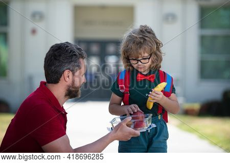 Little Schoolboy Eating Tasty Lunch Outdoors. Parent And Pupil Of Primary School Schoolboy With Back