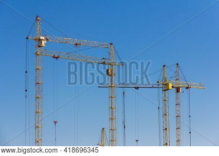 Construction Cranes Against The Blue Sky. Tower Cranes. Lifting Mechanism At A Construction Site. Co