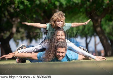 Cute Family Portrait. Portrait Of A Happy Smiling Family Relaxing In Park. Family Lying On Grass In