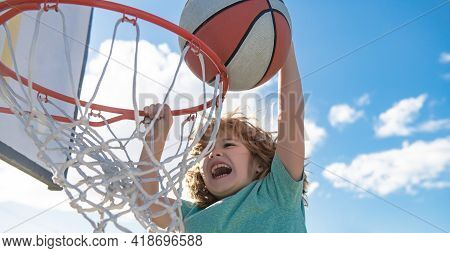 Close Up Image Of Kid Basketball Player Making Slam Dunk During Basketball Game In Floodlight Basket