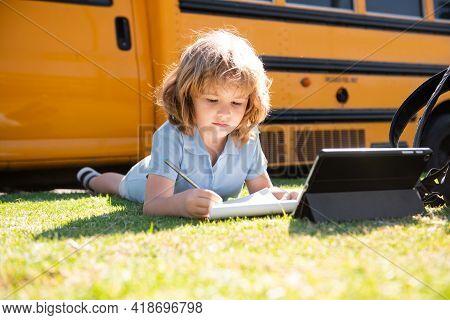 Portrait Of Little Schoolboy Writing Outdoor In Schoolyard Park And Doing Homework.
