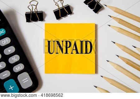 Unpaid The Word Is Written On A Yellow Piece Of Paper On A White Background Near A Calculator And A