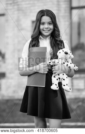 Happy Little Kid Back To School In Uniform Holding Books And Toy Dog In Schoolyard, Knowledge Day
