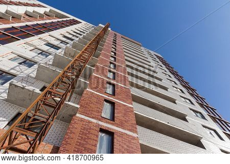 Construction Elevator. The Building's Facade Is Under Construction With A Construction Lift Against