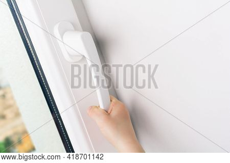 Child Hand Trying To Open A Window Handle Of A Closed White Window - Prevent Child Hazard Concept