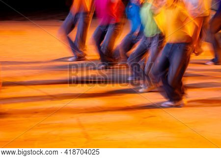 Unrecognised Group Of People Dancing On A Stage. Blurred Motion Of Dancers