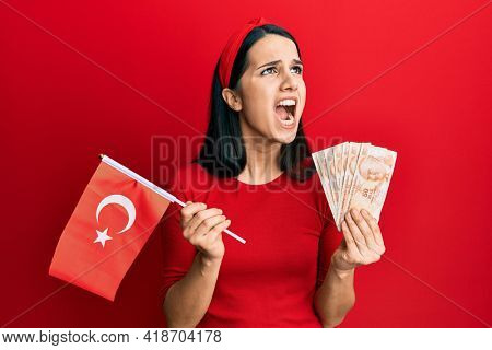 Young hispanic woman holding turkey flag and liras banknotes angry and mad screaming frustrated and furious, shouting with anger looking up.
