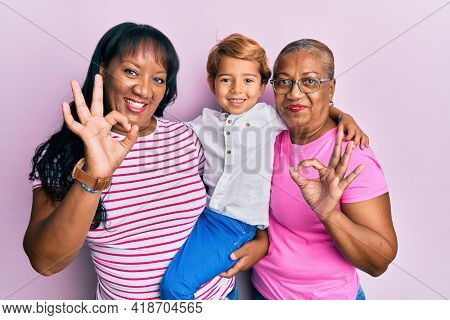 Hispanic family of grandmother, mother and son hugging together doing ok sign with fingers, smiling friendly gesturing excellent symbol