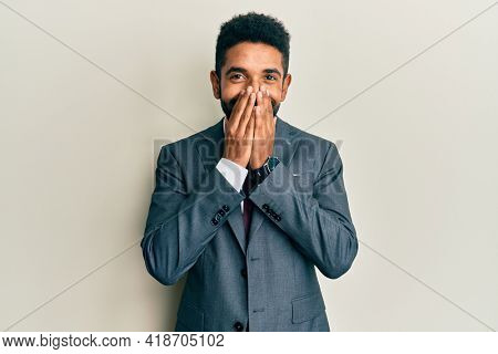 Handsome hispanic man with beard wearing business suit and tie laughing and embarrassed giggle covering mouth with hands, gossip and scandal concept