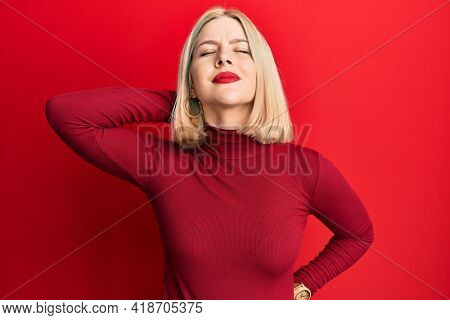 Young blonde woman wearing casual clothes suffering of neck ache injury, touching neck with hand, muscular pain