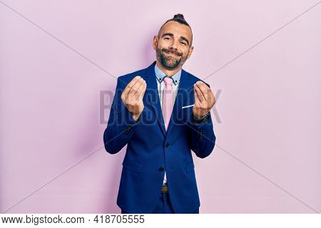 Young hispanic man wearing business suit and tie doing money gesture with hands, asking for salary payment, millionaire business