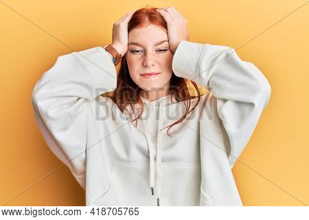 Young red head girl wearing casual sweatshirt suffering from headache desperate and stressed because pain and migraine. hands on head.