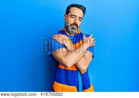 Middle age man with beard and grey hair football hooligan cheering game hugging oneself happy and positive, smiling confident. self love and self care