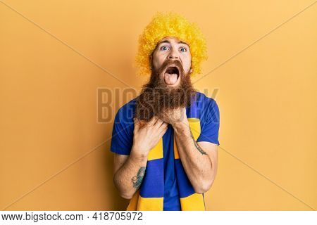 Redhead man with long beard football hooligan cheering game wearing funny wig shouting and suffocate because painful strangle. health problem. asphyxiate and suicide concept.
