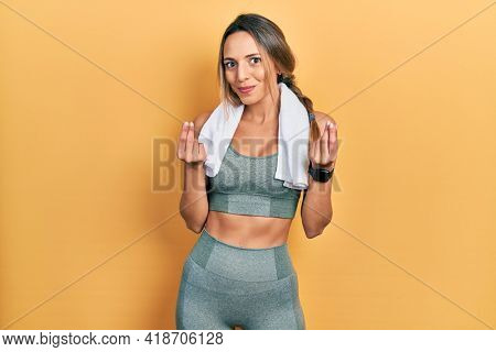 Beautiful hispanic woman wearing sportswear and towel doing money gesture with hands, asking for salary payment, millionaire business