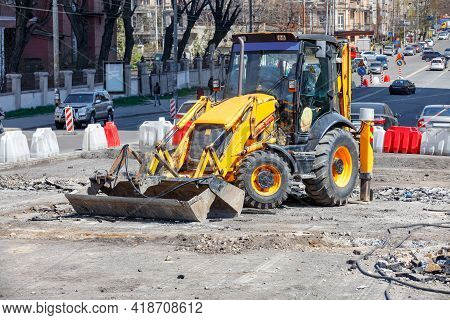 A Road Tractor With Attachments For Repairing The Roadway Stands On A Working Platform Against The B