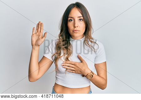 Young brunette woman wearing casual white t shirt swearing with hand on chest and open palm, making a loyalty promise oath