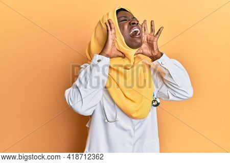 Beautiful african young woman wearing doctor uniform and hijab shouting angry out loud with hands over mouth
