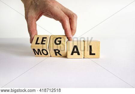 Moral Or Legal Symbol. Businessman Turns Wooden Cubes And Changes The Word 'moral' To 'legal' On A B