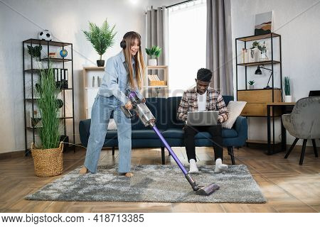 Happy Caucasian Woman Listening Music In Wireless Headphones While Cleaning Carpet With Modern Vacuu